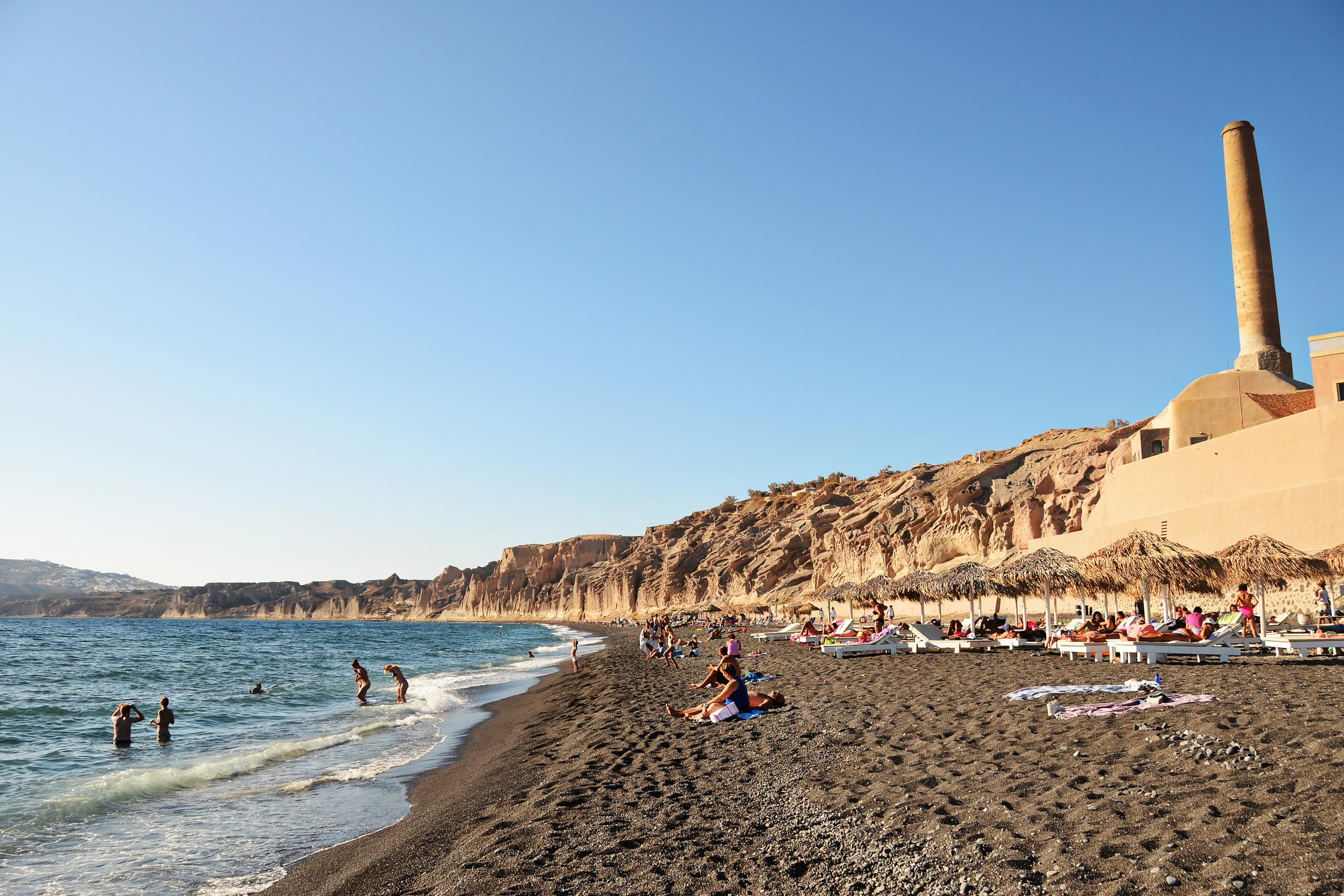 A black beach in Vlychada with the Santorini Arts Factory on the right.