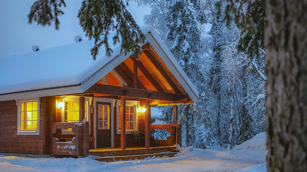 Knus houten huisje bedekt onder Laplandse sneeuw