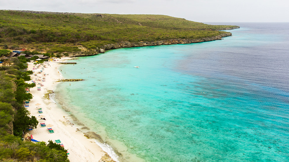 Uitzicht op het felblauwe water van strand Porto Marie in Curaçao
