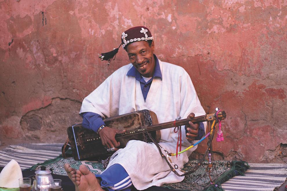 Lokale straatmuzikant voor roze muur in Marrakech
